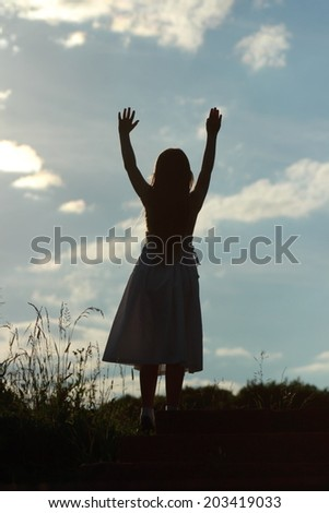 Silhouette of of a little girl on nature background at sunset