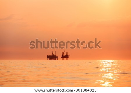 Silhouette of oil platform at sunset