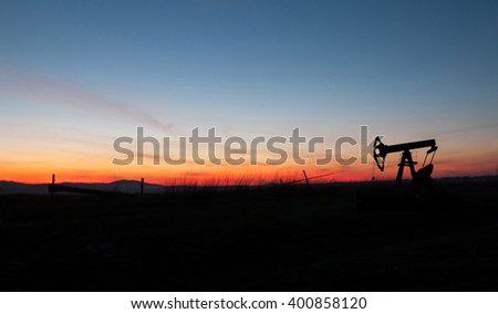 silhouette of oil pump from oil field - stock photo