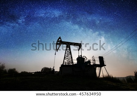 Silhouette of oil pump is working on the oil field in the night under sky with stars and Milky Way. Petroleum industry equipment - stock photo