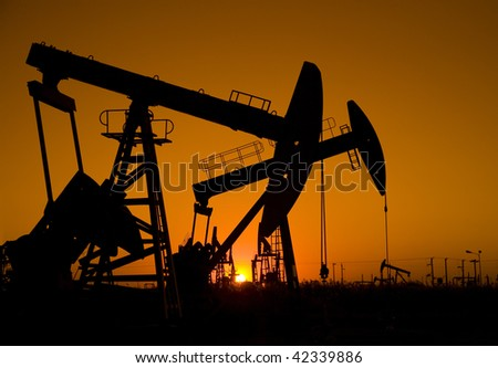 Silhouette of oil pump jack - stock photo
