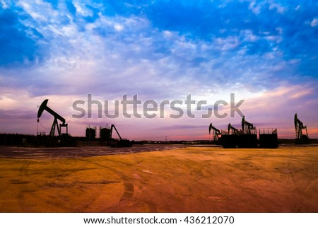 Silhouette of Oil pumps at oil field with nice sunset sky background - stock photo