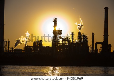 silhouette of oil refinery at sunset - stock photo