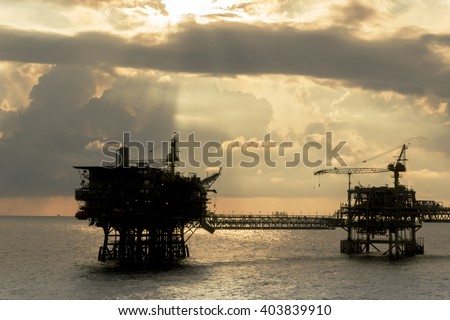Silhouette of oil rigs connected with bridge in the evening at oilfield - stock photo