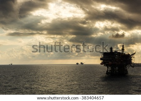 Silhouette of oil rigs during sunrise