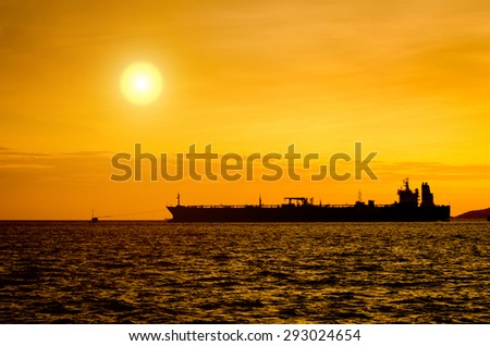 Silhouette of Oil Tanker in the sea at sunset - stock photo