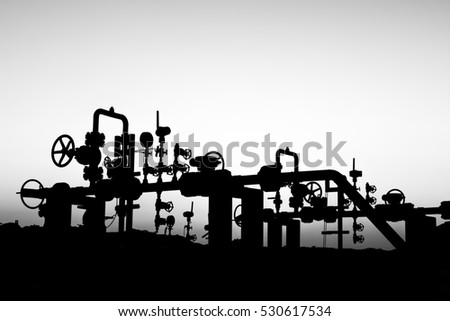 Silhouette of oil well manifold at sunset blue hour in oilfield - black and white