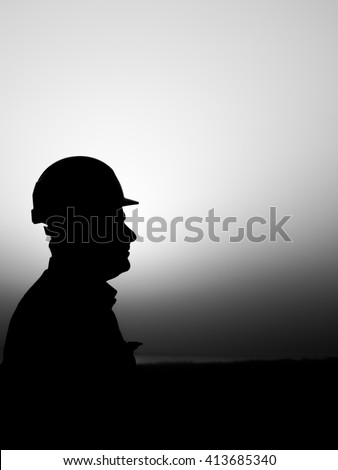 Silhouette of oilfield worker in oilfield  - black and white - sunset - stock photo