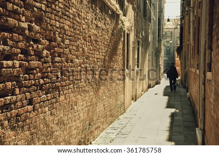 Silhouette of  old man going on narrow street in shining sun rays. (Venice, Italy) A game of light and shadow. Selective focus on the brick wall. Toned photo. - stock photo