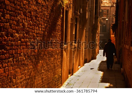 Silhouette of  old man going on narrow street in shining sun rays. (Venice, Italy) A game of light and shadow. Selective focus on the brick wall. Golden sunset. Toned photo. - stock photo