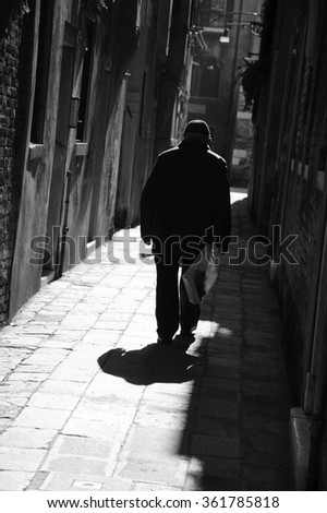 Silhouette of  old man going on narrow street in shining sun rays. (Venice, Italy) A game of light and shadow. Light spots. Aged photo. Black and white.