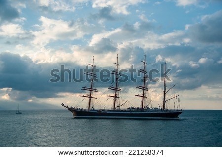Silhouette of old sailing ship  on sunset. Sea landscape with sailboat of the skyline. Romantic trip on the tall ship during the sea sunset. Historic three-masted sailing ship at cloudy sky. - stock photo