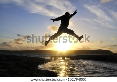 Silhouette of one man jumping over water at the beach. - stock photo