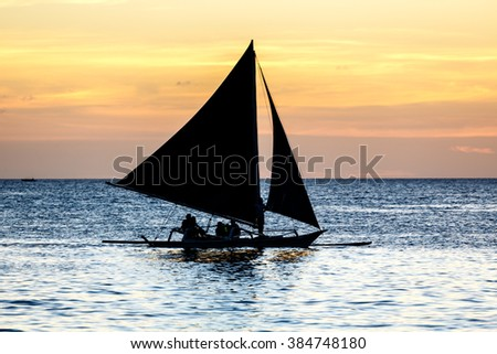 Silhouette of outrigger sailboat at sunset in Philipines - stock photo