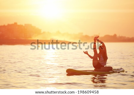 Silhouette of paddle surf yoga at the amazing sunset over the sea, spiritual yoga meditation on the beach - stock photo