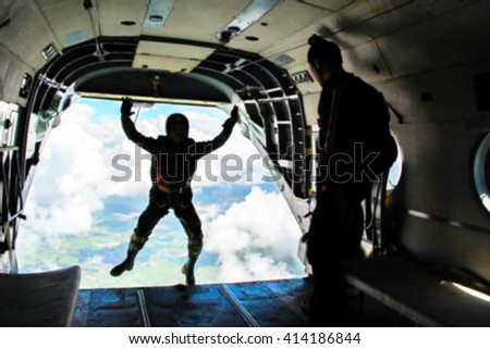 Silhouette of parachute soldier on helicopter blur image - stock photo