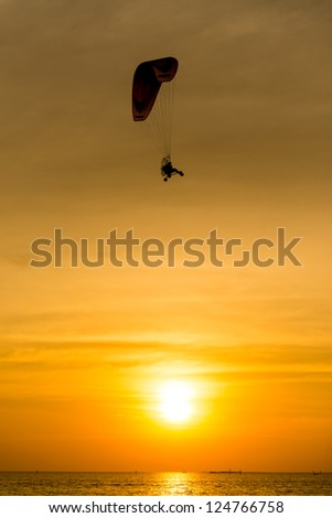 Silhouette of paraglider at sunset - stock photo