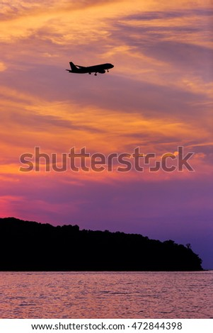 Silhouette of Passenger Airplane Landing at sunset above the sea