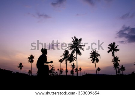 Silhouette of people and coconut tree with twilights sky