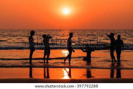 Silhouette of people at sunset, Goa.