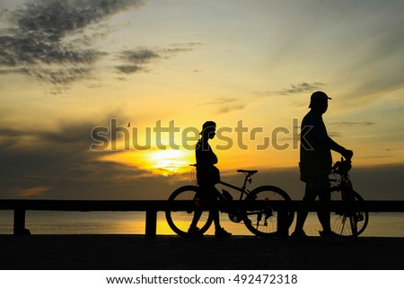 silhouette of people enjoy sunrise on the beach in the morning