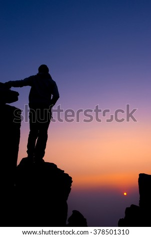 Silhouette of people Hike on the peak of rocks mountain look at sunset