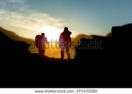 silhouette of people hiking up a mountain, set against a dramatic sky  - stock photo