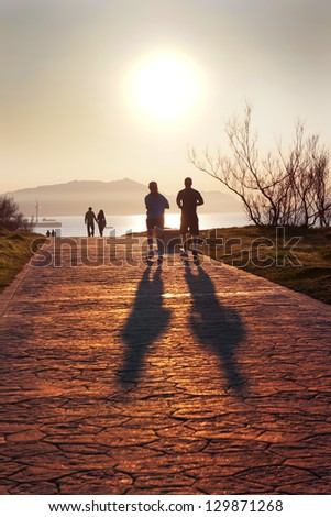 silhouette of people jogging and walking in Getxo park at sunset - stock photo
