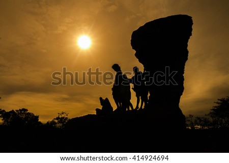 silhouette of people on the cliff