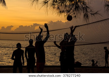 Silhouette of people playing beach volleyball at sunset. Cuba - stock photo
