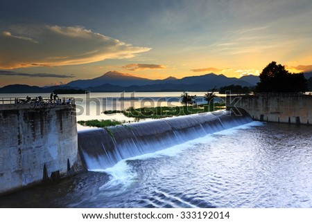 Silhouette of people view on the water dam at sunset - stock photo