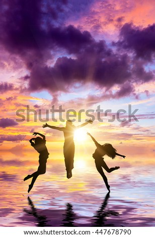 Silhouette of people walking and jumping on the beach at sunset - stock photo