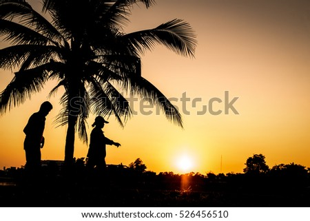 Silhouette of people walking for exercise in park at sunset