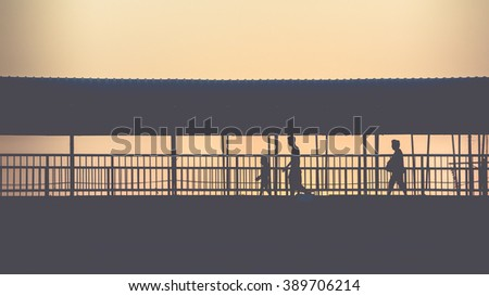 Silhouette of people walking on overpass commuting to work in the early morning in vintage worm tone. - stock photo