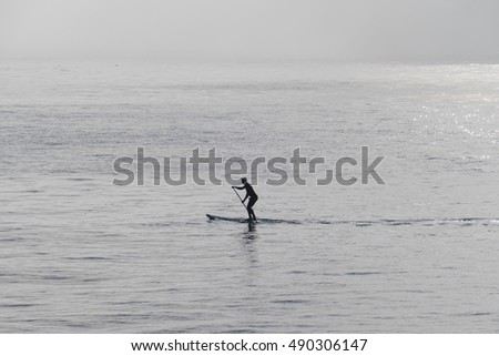 Silhouette of person on a stand up paddle board in a cold morning in Santa Cruz