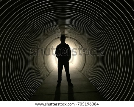 Silhouette of person standing in tunnel