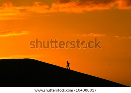 Silhouette of person walking up hill at sunset