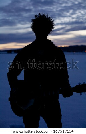 Silhouette of person with guitar at winters sunset - stock photo