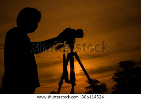 Silhouette of photographer and cameraman shot on a tripod at the - stock photo