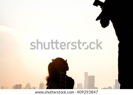 Silhouette of photographer and model at the high building