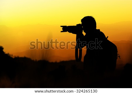 Silhouette of photographer during in sunset with mountains background