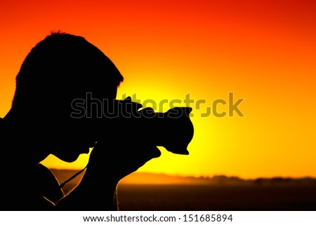 Silhouette of photographer hand holding camera with  lens at sunset.
