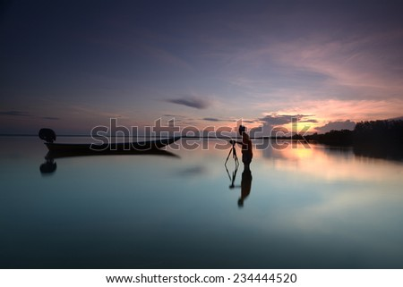 Silhouette of photographer looking to the boat near the beach when the sun goes down - stock photo