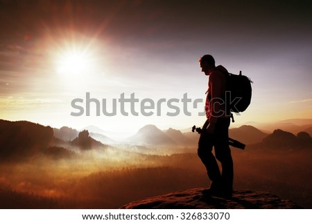 Silhouette of photographer overlooking a blanket of fog over valley to sun - stock photo