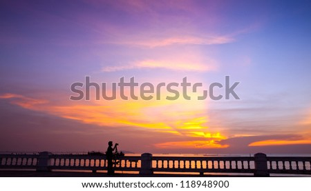 Silhouette of photographer shooting sea at twilight background