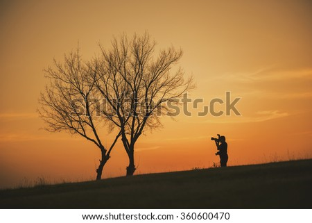 silhouette of photographer taking photo at sunset beside the tree.