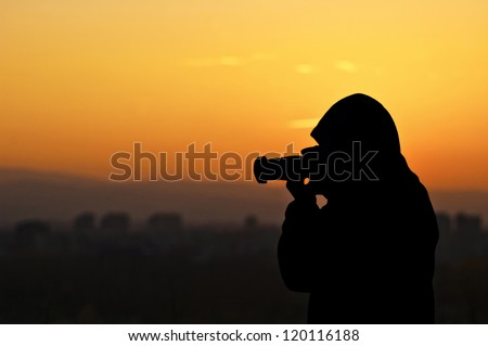 Silhouette of photographer taking pictures of sunset - stock photo