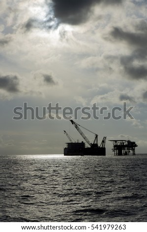 Silhouette of pipe lay barge and oil and gas platform with cloudy sky in the middle of the sea.