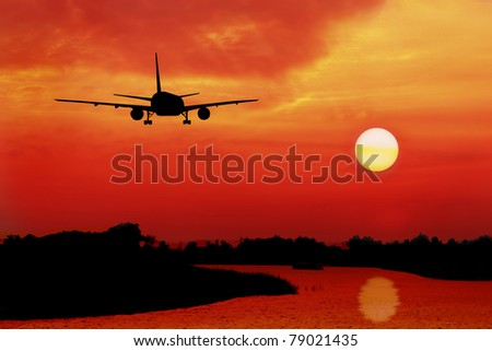 silhouette of plane fly over land and river during sunrise