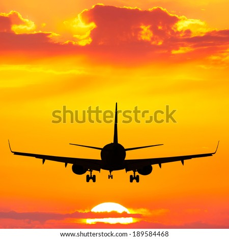 Silhouette of plane flying up at orange sunset